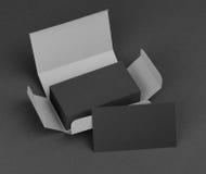 Tarjetas de visita negras en la caja gris Imagenes de archivo