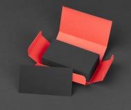 Tarjetas de visita negras en la caja roja Fotos de archivo