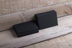 Tarjetas de visita negras en viejo fondo de madera Imagen de archivo libre de regalías