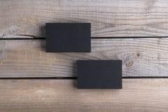 Tarjetas de visita negras en viejo fondo de madera Fotos de archivo libres de regalías