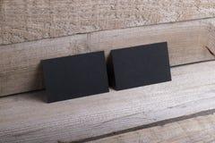 Tarjetas de visita negras en viejo fondo de madera Fotos de archivo