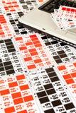 Tarjetas del bingo y un ordenador portátil Imagen de archivo