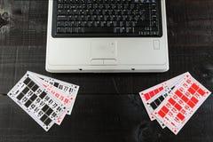 Tarjetas del bingo y un ordenador portátil Fotografía de archivo libre de regalías