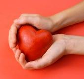 Tarjetas del día de San Valentín - corazón rojo en manos fotografía de archivo