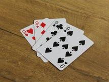 Tarjetas del póker en un backround de madera, el sistema de nines de clubs, diamantes, espadas, y corazones Imágenes de archivo libres de regalías