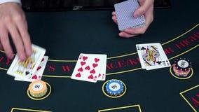 Tarjetas del trato del crupié en la tabla con los microprocesadores, casino, cámara lenta metrajes