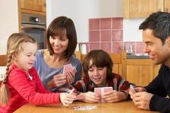 Tarjetas que juegan de la familia en cocina Imágenes de archivo libres de regalías