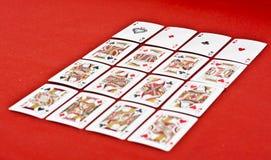 Tarjetas que juegan en tela roja Fotos de archivo libres de regalías