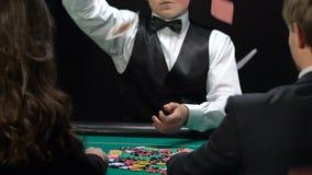 Tarjetas que lanzan del crupié en la gente rica de la tabla que juega el póker, negocio de juego almacen de metraje de vídeo