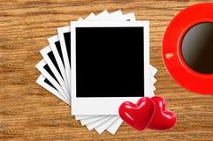 Tarjetas vacías de la foto, taza de café y corazones rojos en la madera Fotos de archivo