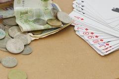 Tarjetas y dinero de juegos en la tabla Imágenes de archivo libres de regalías