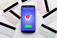 Tarjetas y smartphone de crédito que mienten en una tabla de madera Imagen de archivo libre de regalías