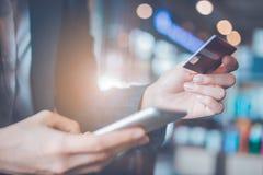 Tarjetas y smartphones de crédito del uso de la mano de la mujer de negocios Foto de archivo libre de regalías