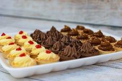 Tarlets saborosos com o confi do creme e da framboesa da baunilha, o creme do chocolate e o toffie foto de stock