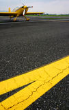 Tarmac. Yellow lines on the tarmac with aerobatics plane in background Stock Photos
