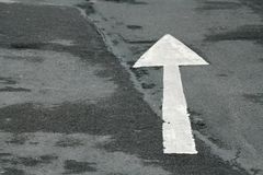 Tarmac Arrow. A white arrow painted on damp tarmac stock photo