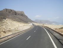 Tarmac road along beach in desert with mountains. Cape Verde royalty free stock photo