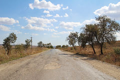Tarmac road in the countryside with potholes along the picturesque meadows in Crimea. Stock Images