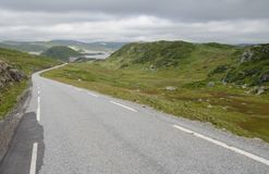 Hilly lanscape with tarmac road and grassy bogs, Norway Royalty Free Stock Image