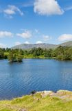 Tarn Hows in the Lakes Cumbria with mountains in the background Royalty Free Stock Photo