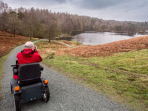 Tarn hows tramper. Tarn Hows, Coniston, UK. April 5th 2016. Photographer enjoying the great outdoors at Tarn Hows using a Tramper Mobility Scooter Stock Photos