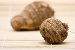 Taro root. Fresh whole taro root on bamboo mat Stock Photo