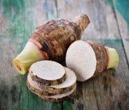 Taro root on wooden. Fresh taro root on wooden stock photos