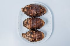 Taro roots on plate on white background stock image