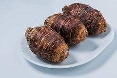 Taro roots on plate on white background stock photo