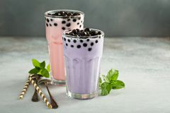 Taro and strawberry milk bubble tea in tall glasses. Taro and strawberry milk bubble tea with ice in tall glasses royalty free stock photo