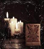 Tarokkortet med jäkel mot defocused stearinljusbakgrund Arkivfoto