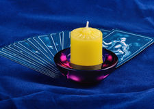 Tarot. The pack tarot lays on a dark blue fabric, near locates a candle royalty free stock image