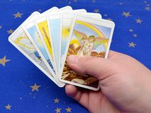 Tarot Cards. Fortune-teller holding tarot cards in hand on blue background stock images