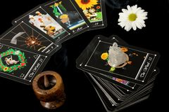 Tarot Cards. Deck of tarot cards spread on table, with crystal, flower and incense burner stock image