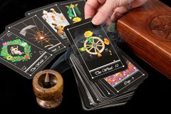 Tarot Cards. Deck of tarot cards spread on table, with wooden box and incense burner - hand holding card Stock Photos