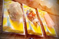 Tarot cards on a board. Tarot cards, dowsing tool and crystals on a wooden board stock photos
