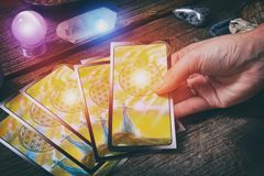 Tarot cards on a board. Tarot cards in hand, dowsing tool and crystals on a wooden board royalty free stock photo