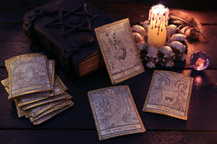 The tarot cards with book and candle. The tarot cards with crystal, candle and book. Halloween and magic still life, fortune telling seance or black magic ritual Royalty Free Stock Photo