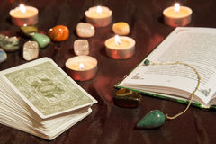 Tarot cards with book and pendulum. Moscow, Russia - December 4, 2016: Tarot card deck with book, green pendulum and candles. Esoteric background Royalty Free Stock Photos