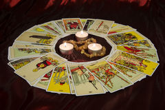 Tarot cards and burning candle. Moscow, Russia - December 4, 2016: Rider-Waite tarot cards and burning candle in center. Esoteric background Royalty Free Stock Photo