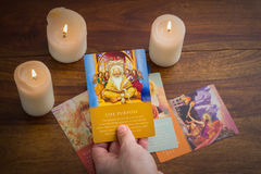 tarot cards and burning candle on wooden table stock images