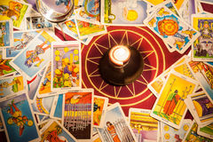 Tarot cards with a candle. Tarot cards on a pentagram with a candle and a crystal ball in the center royalty free stock image