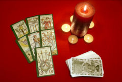Tarot cards with candles on red textile. Old styled tarot cards with candles on red textile Stock Photo