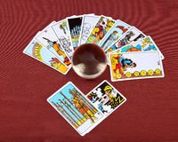 Tarot cards and crystal bowl. On red fabric background Stock Images