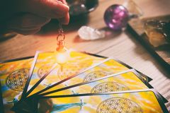 Tarot cards and dowsing. Tarot cards dowsing tool in hand and crystals as a concept of psychic advisor or ways of divination royalty free stock images