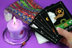 Tarot Cards in hand. Hand holding tarot cards with deck and candle in background Royalty Free Stock Images