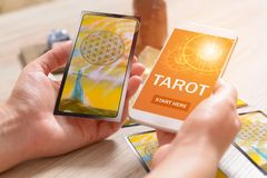 Tarot cards and mobile phone. Tarot cards and smartphone with modern fortunetelling application on screen as a concept of psychic advisor or newest ways of stock photo