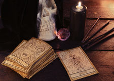 The tarot cards with skull and black candle. Human skull, crystal, black candle and the tarot cards on wooden table. Halloween and magic still life, fortune Royalty Free Stock Photos