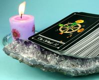 Tarot Deck Clearing. Clearing or cleansing tarot cards on amethyst crystal geode, with candle in background Royalty Free Stock Photo