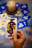 Tarot reading. Esoteric reading of tarot with runes, astrological cards and candle in background Stock Photos